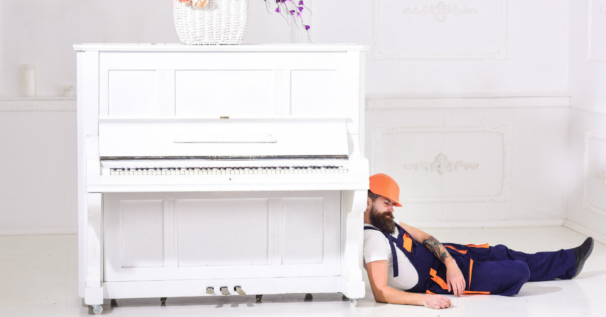 man resting while moving a piano